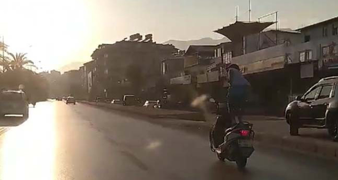 Seyir halindeki motosikletin üzerinde ayağa kalkıp hayatını riske attı